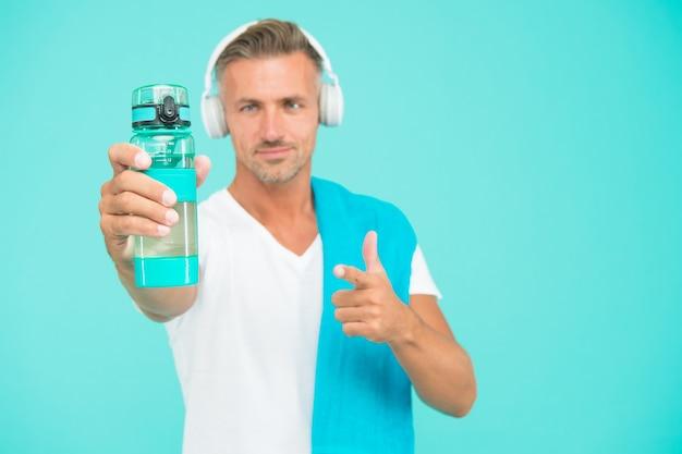 健康的な生活様式。男はタオルで手入れの行き届いたアスリート。ウォーターボトルとヘッドフォンを備えたスポーツマンジムインストラクター。ジムの美学。成熟しているが、まだ良い状態です。より良い健康のためにジムで運動する。