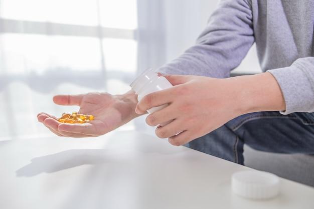 健康的なライフスタイル、薬、栄養補助食品と人々の概念 - タラの肝油カプセルと水ガラスで丸薬を保持している男性の手を閉じる