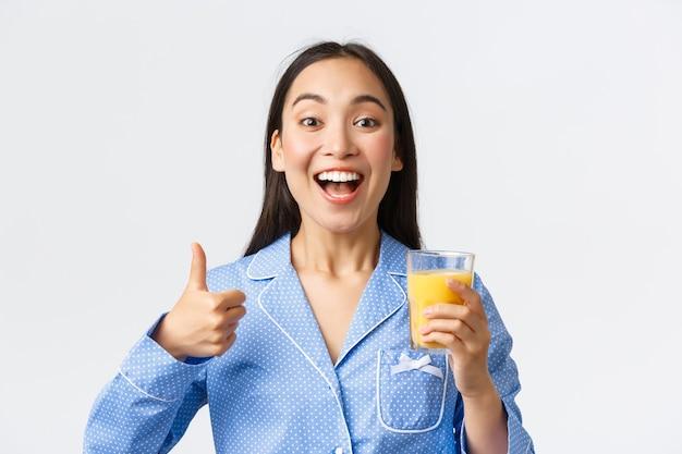 Stile di vita sano, routine mattutina e concetto di persone. primo piano di una bella ragazza asiatica eccitata in pigiama che ha l'abitudine di bere succo d'arancia fresco pieno di vitamine, mostrando il pollice in su.