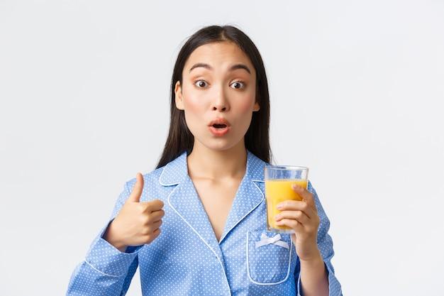 Stile di vita sano, routine mattutina e concetto di persone. primo piano di una ragazza asiatica sorpresa e soddisfatta che sembra stupita mentre mostra il pollice in su e prova il succo d'arancia fresco, sfondo bianco.