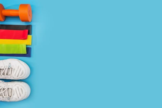 健康的なライフスタイル、栄養、スポーツのコンセプト。青い背景にダンベル、フィットネスラバーバンド、スニーカー。