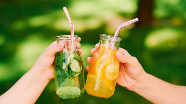 健康的な生活様式。有機デトックスドリンク。女性は健康のために新鮮な天然レモネードを飲みます。
