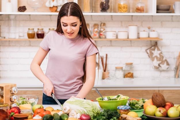 건강한 생활. 유기농 저녁 식사 레시피. 맞는 음식. 식사를 준비하는 부엌 카운터에서 젊은 여자.