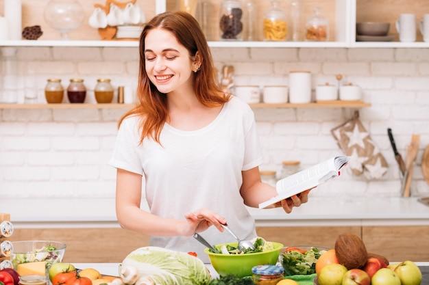 건강한 생활. 유기농 저녁 식사 레시피. 적합한 녹색 식품. 식사를 준비하는 손에 책을 가진 젊은 여자를 웃 고.