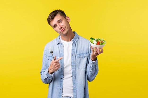 건강한 생활 방식, 사람, 음식 개념. 마지못해 잘생긴 청년이 역겨운 샐러드를 손가락으로 가리키고, 이것을 먹기를 꺼려하고, 불만스럽게 웃으며 고개를 기울이고 슬픈 노란색 배경을 가지고 있습니다.