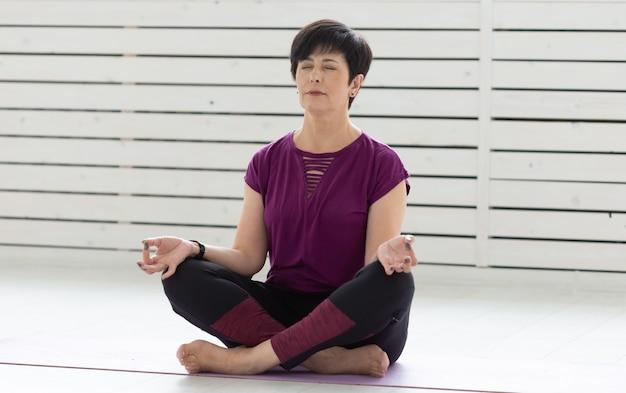 健康的なライフスタイルの人々と蓮のポーズでヨガを練習するスポーツコンセプトの魅力的な中年女性
