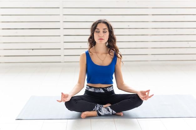健康的なライフスタイル、人々、スポーツのコンセプト-蓮華座でヨガを練習する魅力的な女性。
