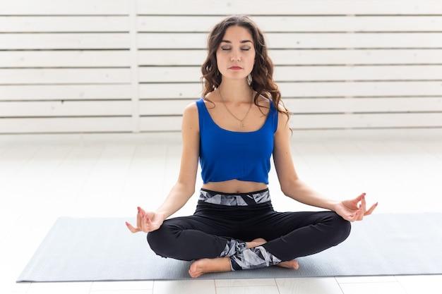 健康的なライフスタイル、人々、スポーツのコンセプト。蓮華座でヨガを練習する魅力的な女性。