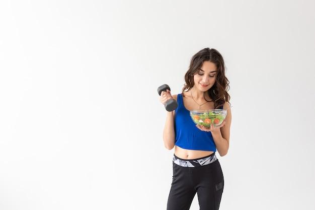 건강한 생활 방식, 사람, 스포츠 개념 - 야채와 아령을 가진 건강한 젊은 여성이 건강한 피트니스와 식습관을 촉진합니다.