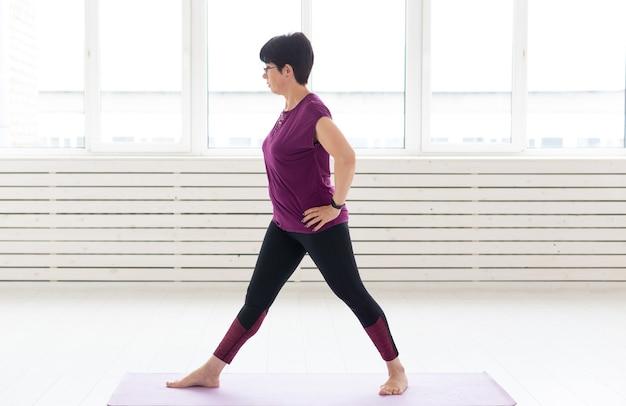 健康的なライフスタイル、人々、スポーツのコンセプト-ヨガをしている中年の女性。