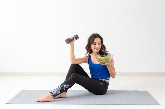 건강한 생활 방식, 사람, 스포츠 개념 - 야채와 아령을 가진 건강한 여성의 초상화.