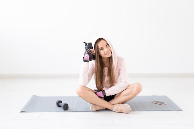 健康的なライフスタイル、人々、スポーツのコンセプト-ハードワークアウトの後にヨガマットに座って水を飲む笑顔の女性。