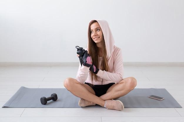 건강한 라이프 스타일, 사람과 스포츠 개념-열심히 운동 후 요가 매트와 식수에 앉아 웃는 여자.