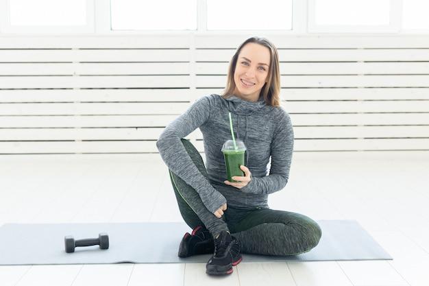 健康的なライフスタイル、人々、スポーツのコンセプト-スポーツのために健康的なジュースを飲む女性と