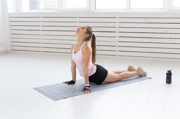 健康的なライフスタイル、人々、スポーツのコンセプト-ストレッチを伴う女性のトレーニング。
