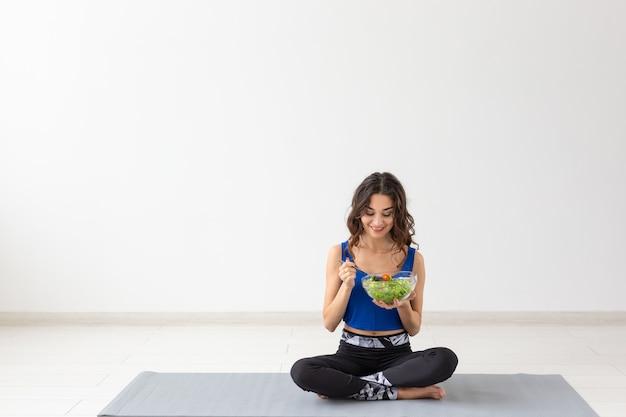 Концепция здорового образа жизни, людей и спорта - женщина йоги с миской овощного салата после
