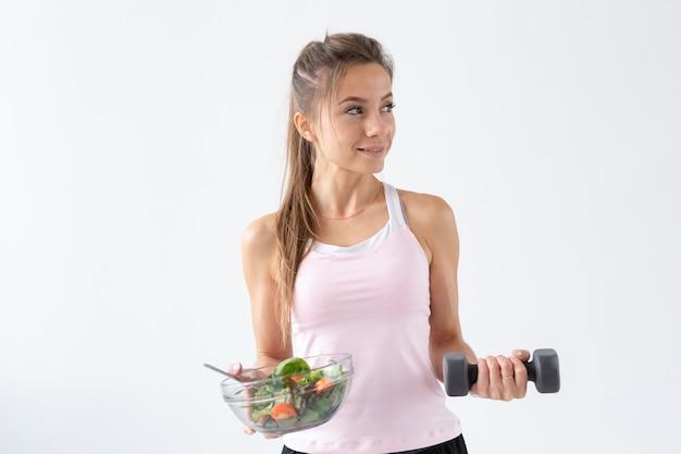 건강한 생활 방식, 사람들의 개념 - 한 손에는 샐러드 한 접시, 다른 손에는 아령. 미소와 피트니스 슈트.