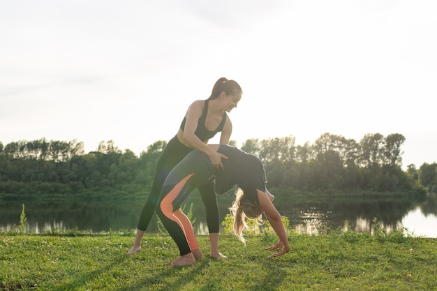 Healthy lifestyle and people concept - flexible women doing yoga in the summer park