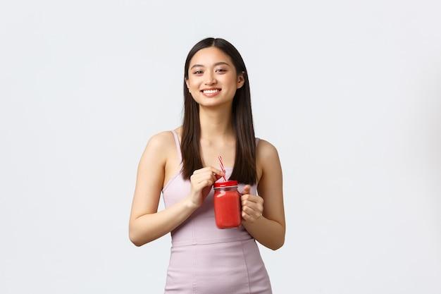 건강한 라이프 스타일, 사람들의 감정과 여가 개념. 드레스에 밝은 미소 아시아 여자, 스무디를 마시고 기쁘게 카메라를 웃고