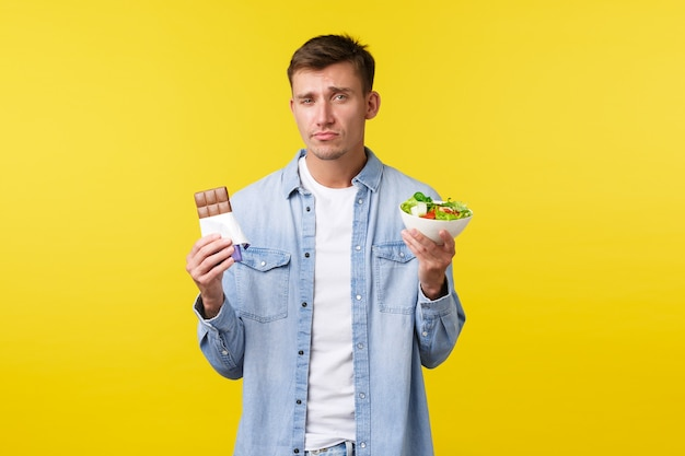 Healthy lifestyle and people emotions concept. gloomy handsome caucasian guy showing salad in bowl and candy bar, grimacing as reluctant eat diet food, standing yellow background