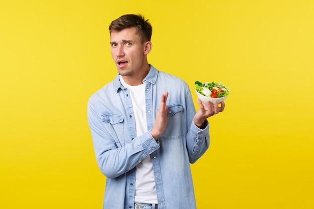 Stile di vita sano, persone e concetto di cibo. all'uomo bello allarmato e infastidito non piace mangiare questo, mostrando il gesto di rifiuto alla ciotola con insalata disgustosa, in piedi su sfondo giallo.