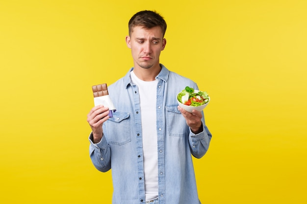 Healthy lifestyle, people and food concept. displeased and reluctant handsome sad guy want eat candy bar and looking with disgust at bowl with salad, sit on diet, standing yellow background.