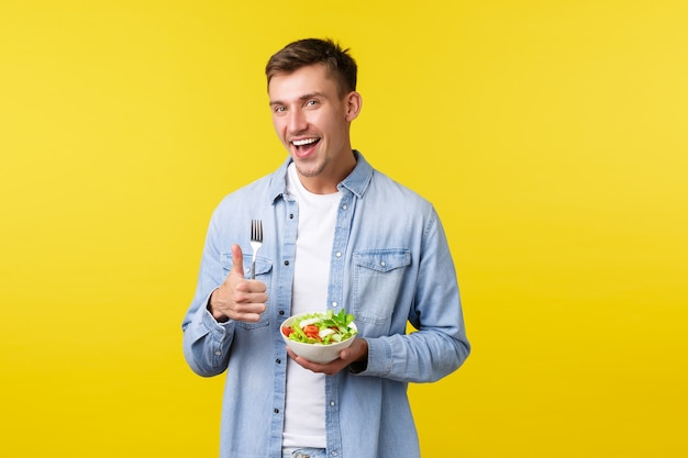 Healthy lifestyle, people and food concept. happy smiling man showing thumbs-up satisfied with delicious breakfast, eating salad, being on diet, trying stay fit, standing yellow background.