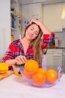 Здоровый образ жизни, портрет белокурой кавказской женщины, сжимающей апельсины, делая свежий апельсиновый сок