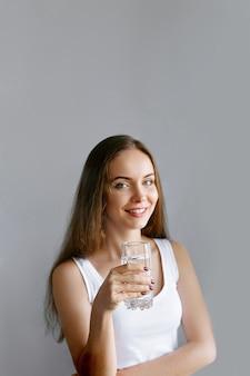 健康的な生活様式。孤立したスタジオの背景にポーズをとって、幸せな笑顔の若い女性の肖像画、水ガラスを保持します。美しい少女の肖像画。女性モデルのポーズ。