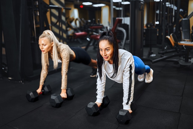 Healthy lifestyle portrait of two young athletic girls doing plank in the gym