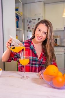 Здоровый образ жизни, довольно белокурая кавказская женщина в красной клетчатой рубашке помогает себе свежий апельсиновый сок