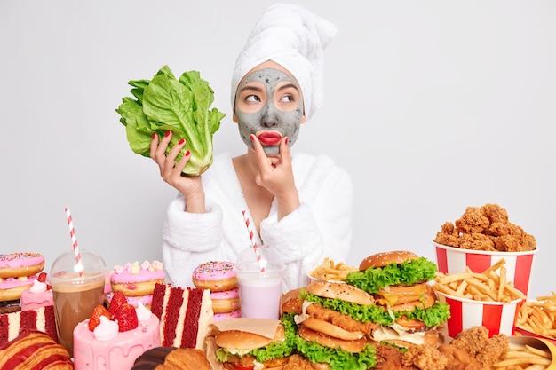건강한 라이프 스타일 적절한 영양 유혹 개념입니다. 생각에 잠긴 아시아 여성은 녹색 상추 샐러드를 들고 건강에 좋은 음식과 건강에 해로운 음식 중에서 선택합니다