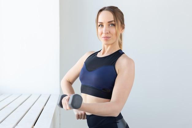 健康的なライフスタイル、スポーツ、フィットネスのコンセプト-ジムでのトレーニング後に休んでいる若い女性。