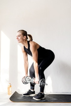 Healthy lifestyle. sport and fitness. young blond woman working out with dumbbells doing deadlift