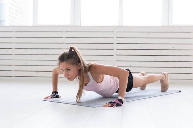 Healthy lifestyle, sport, people concept - a young woman is doing fitness in the gym or home. she is pressing in the sport suit.