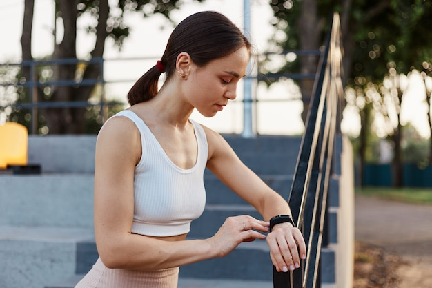 Healthy lifestyle and sport in summer. side view of dark haired woman happy with result of jogging and looks at fitness tracker with concentrated look.