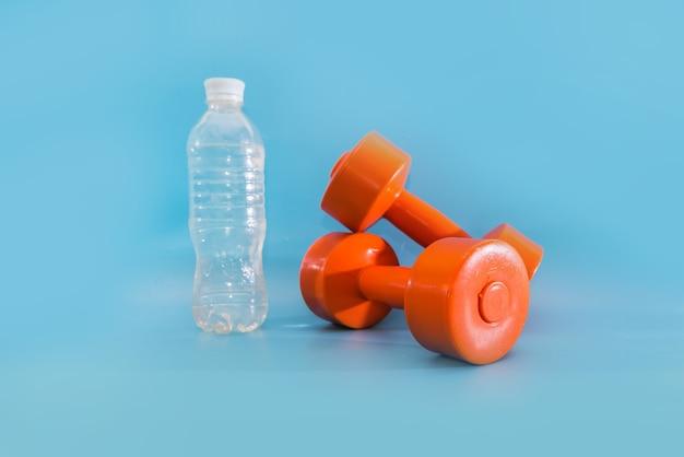 健康的なライフスタイル、スポーツ、スポーツ用品。青い背景にダンベルと水のボトル。