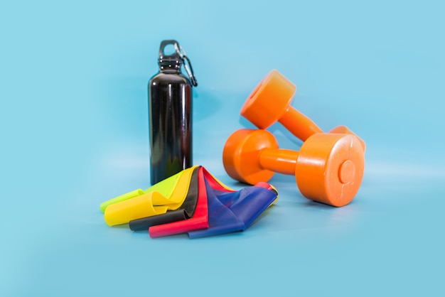 健康的なライフスタイル、スポーツ、スポーツ用品。ダンベル、フィットネスラバーバンド、青い背景のスポーツフラスコ。