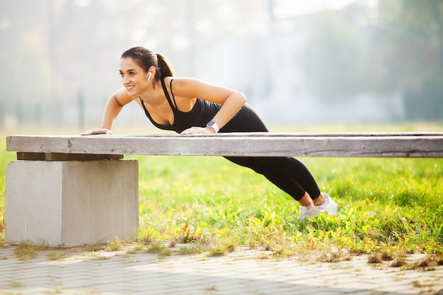 Healthy lifestyle, sports woman doing exercises on bench and listening to music in the urban environment