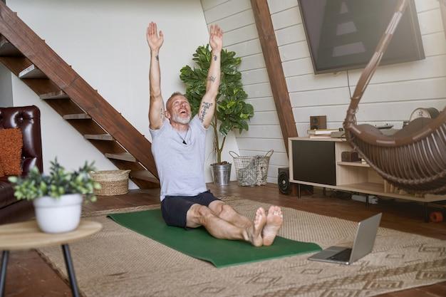 건강한 라이프 스타일 스포티 한 중년 남자는 거실에서 요가 매트에 앉아있는 동안 운동