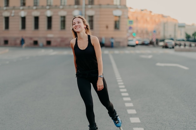 Healthy lifestyle summer leisure active outdoor recreation concept. smiling dark haired young woman enjoys rollerblading as hobby looks into distance wears sportsclothes rides fast on rollers