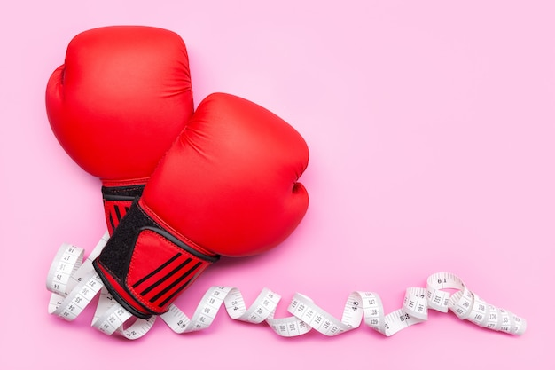 Healthy lifestyle or weight loss concept. boxing gloves and measure tape isolated . copy space
