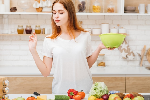 건강한 생활. 체중 감량 레시피. 유기농 야채 구색을보고 샐러드 그릇을 가진 젊은 여자.