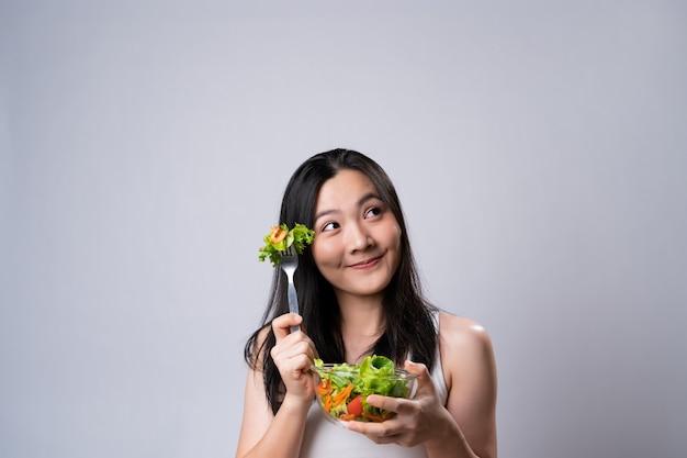 Healthy lifestyle with clean food concept. happy asian woman eating salad isolated over white wall.