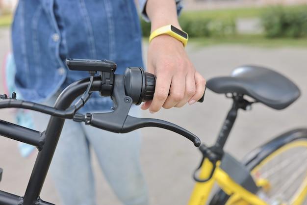 健康的な生活様式。女性は自転車のハンドルバーを保持します