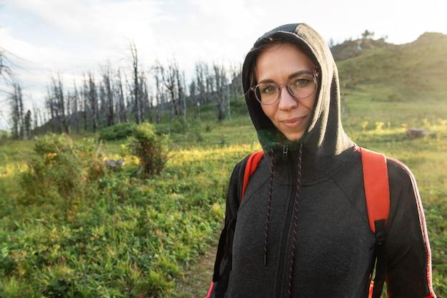 Женщина здорового образа жизни гуляет в горах в летнем лесу