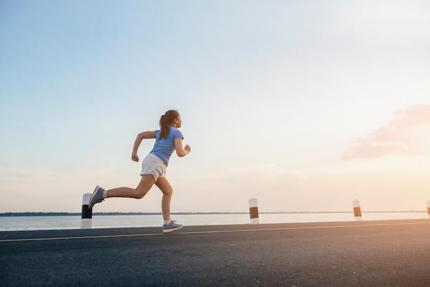 Женщина фитнеса здорового образа жизни молодая бежать на берегу реки.