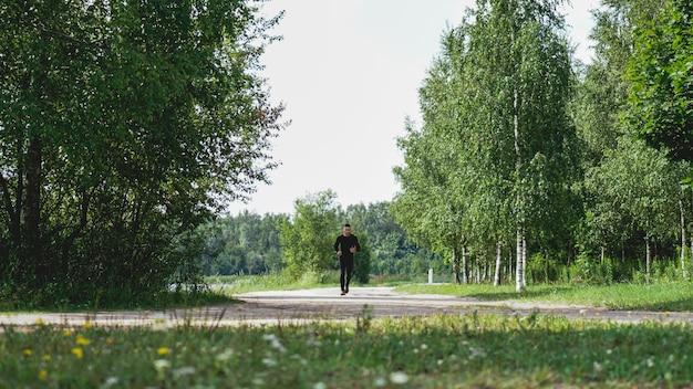 Молодой человек здорового образа жизни работает в зеленом лесу