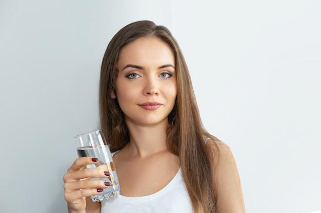 건강 한 생활 양식입니다. 신선한 물 한 잔에서 마시는 젊은 여자. 보건 의료. 음료수. 투명 한 유리를 들고 행복 하 게 웃는 여성 모델의 초상화. 프리미엄 사진