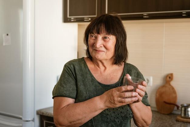 のどが渇いて成熟したキッチンでガラスからミネラルウォーターを飲む健康的な液体かわいいブルネットの女性...
